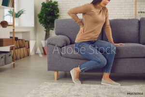Young woman suffers from backache, hurt muscles, physical injury, rheumatism, radiculitis, spine arthritis or pinched nerve attack, tries to get up from sofa but feels sudden pain in lower back